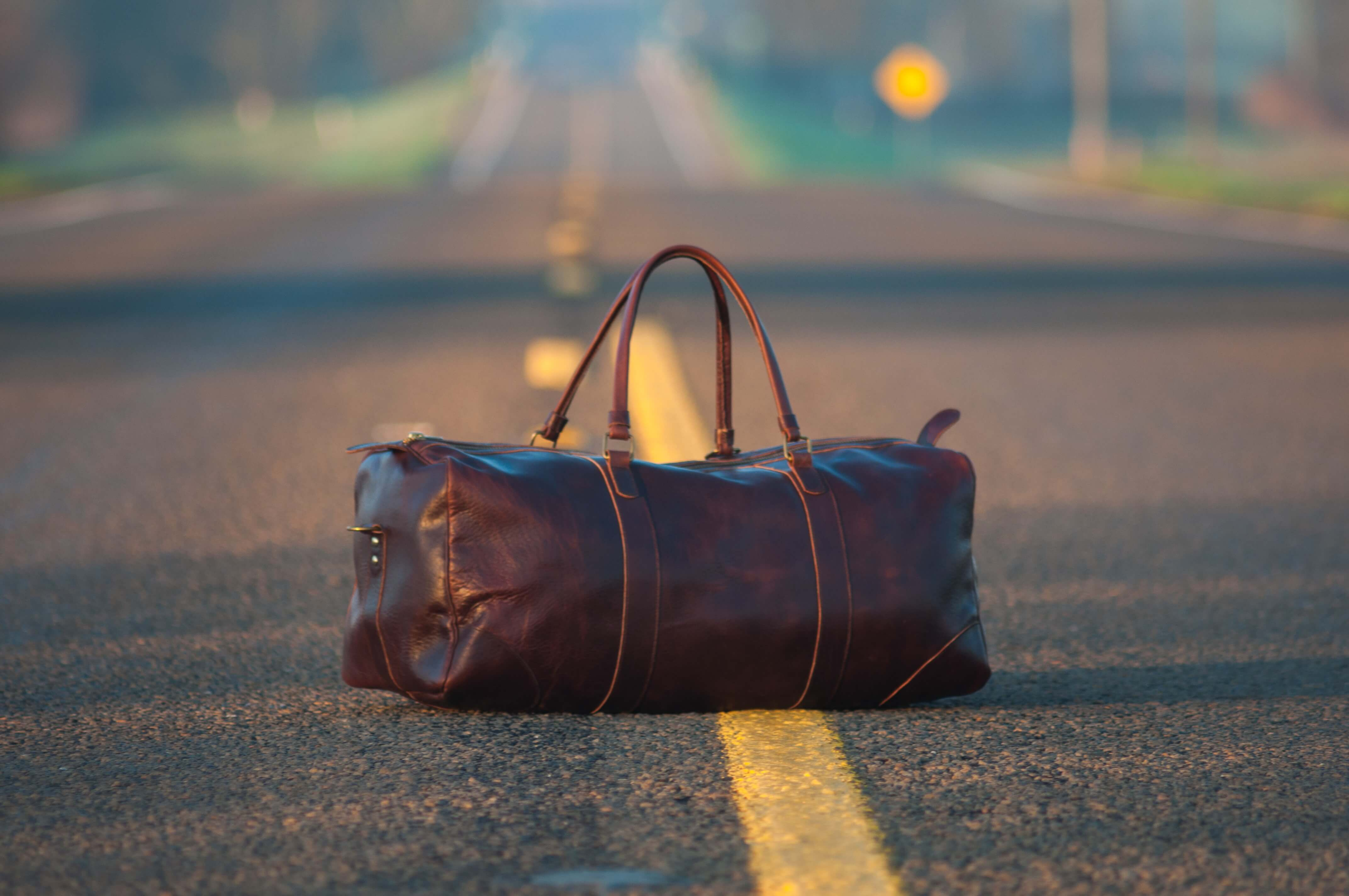 a brown leather bag in the middle of a road illustrates this story on Europe packing list